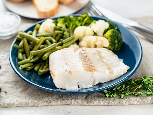 Boiled sea fish cod fillet with vegetables on blue plate, grey wooden table, side view.