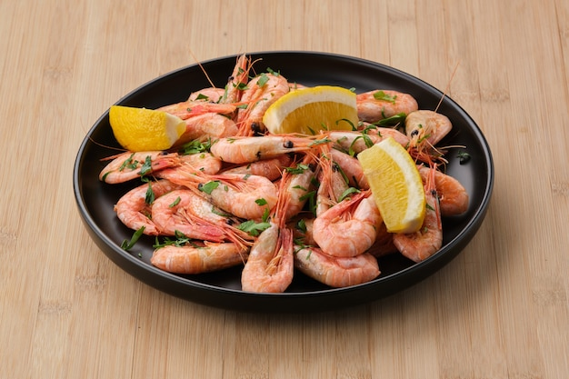 Boiled shrimp garnished with lemon and parsley in a dark plate on a light wooden background