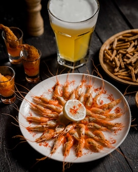 Boiled shrimp with lemon and a glass of cold beer