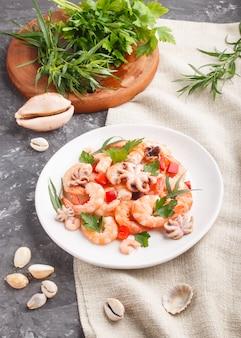 Вареные креветки или креветки и маленькие осьминоги на белой керамической тарелке на черном бетоне и льняном текстиле. вид сбоку.