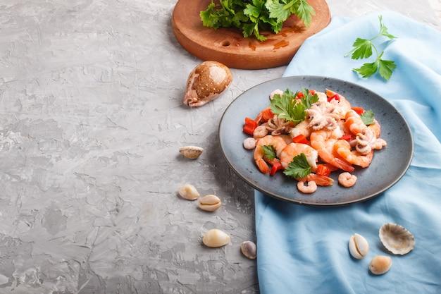 Вареные креветки или креветки и маленькие осьминоги с зеленью на синей керамической тарелке на сером бетоне. вид сбоку.