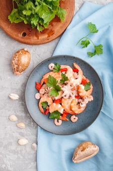 Boiled shrimps or prawns and small octopuses with herbs on a blue ceramic plate on a gray concrete background