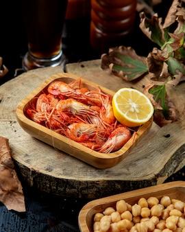 Boiled shrimps served with lemon half in bamboo serving
