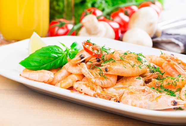 Boiled shrimps with lemon on a plate in a cafe