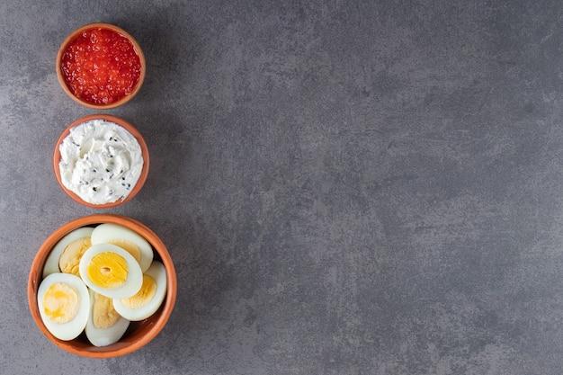 Uova bollite a fette con salse poste su sfondo di pietra.