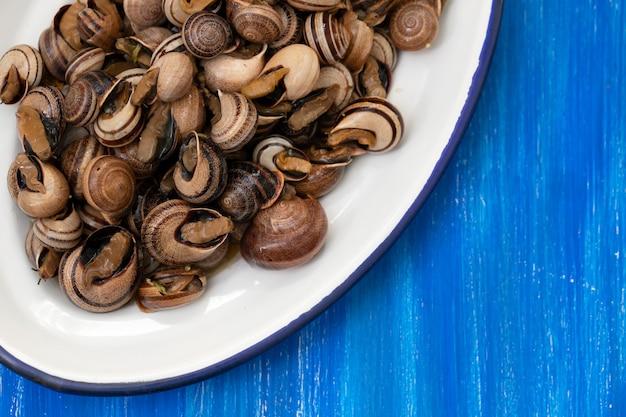 木製の背景に白い皿にハーブと茹でカタツムリ
