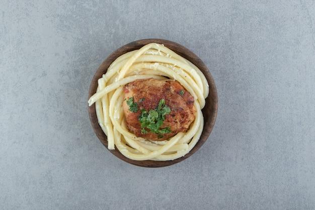 Вареные макароны спагетти и жареный цыпленок в деревянной миске.