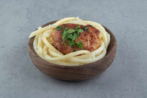 Boiled spaghetti pasta and roasted chicken in wooden bowl.