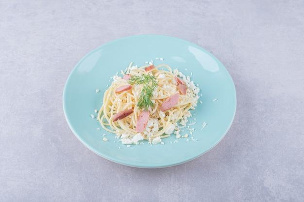 파란색 접시에 슬라이스 소시지와 삶은 스파게티.