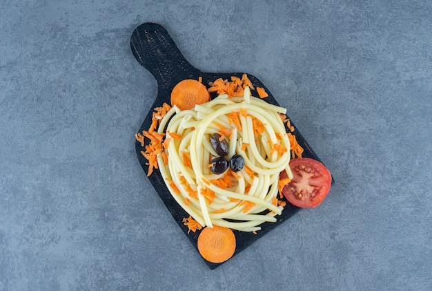 Boiled spaghetti with vegetables on black board.