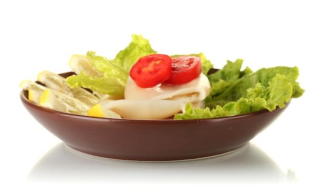 白で隔離されたプレート上の野菜と茹でイカ