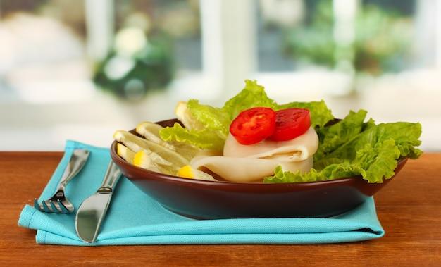 木製のテーブルの皿に野菜とイカの茹で