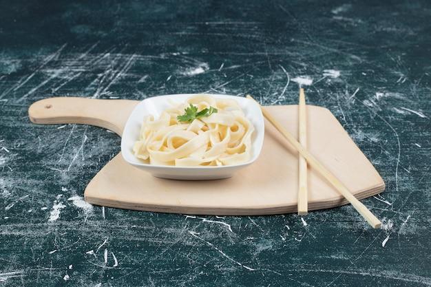 Boiled tagliatelle pasta in white bowl with chopsticks.