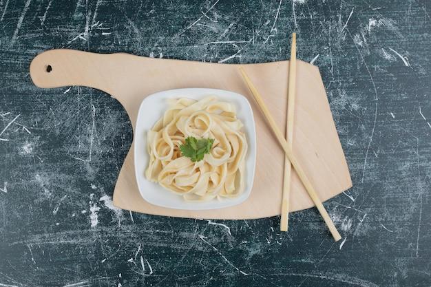 Tagliatelle bollite sul piatto bianco con le bacchette.