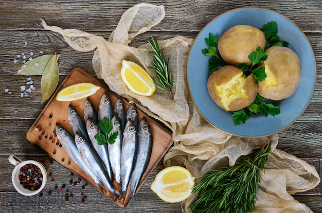 Boiled unpeeled potatoes in skins, a small salted fish of baltic herring, sprats on a wooden table. top view. flat lay