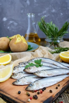 Boiled unpeeled potatoes in skins, a small salted fish of baltic herring, sprats on a wooden table