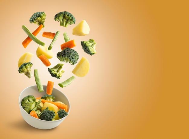 Вареные овощи пролетели над апельсином с копией пространства