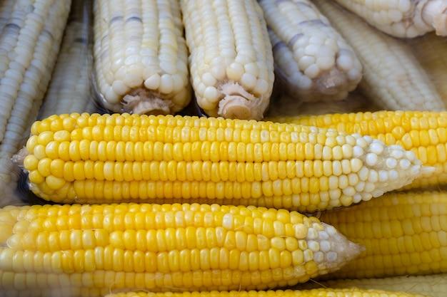 タイの屋台の食品市場で販売されている白と黄色のゆでトウモロコシ、クローズアップ