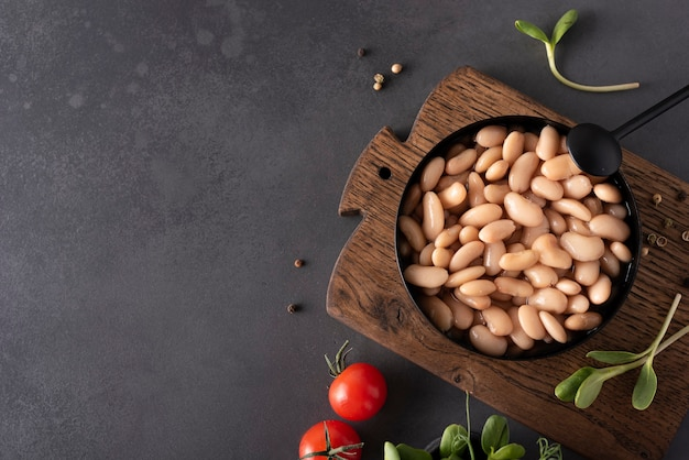 Boiled white beans with spices and herbs in a black bowl, close-up Premium Photo