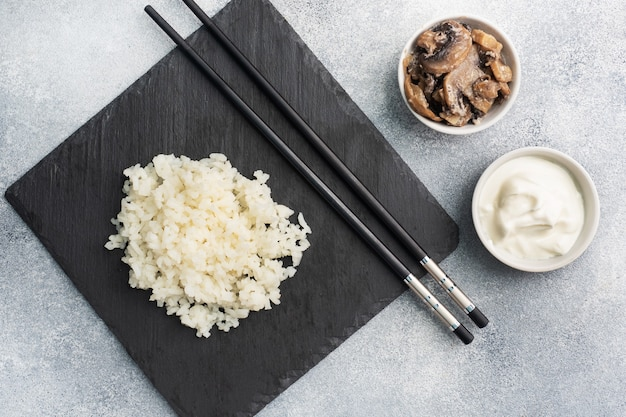 Отварной белый рис и грибы в сметане на черной подставке с палочками для еды