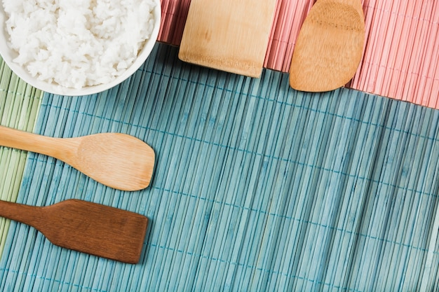 Boiled white rice bowl on different type of wooden spatula over placemat
