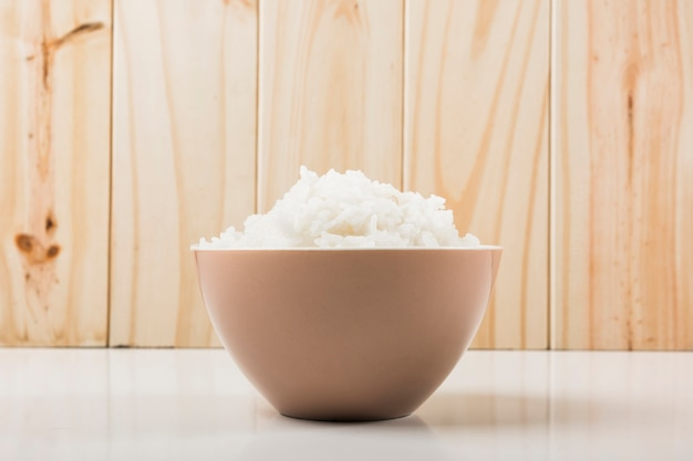 Boiled white rice in the bowl on white table against wooden background