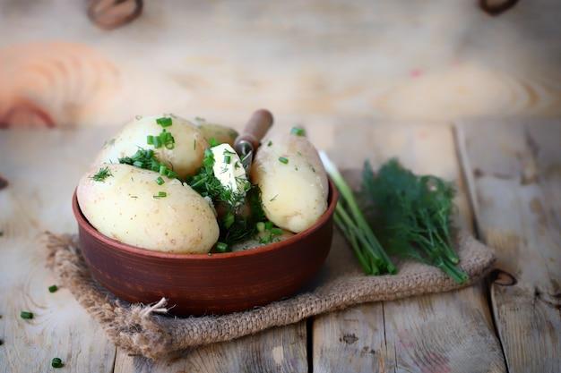 ボウルにハーブとバターを入れて茹でた若いジャガイモ