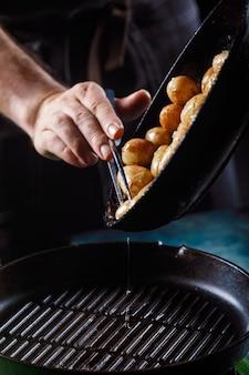 Отварной молодой картофель с маслом и жареный чеснок в деревянной посуде