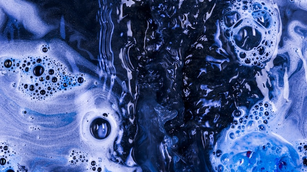 Boiling blue liquid with foam and blobs