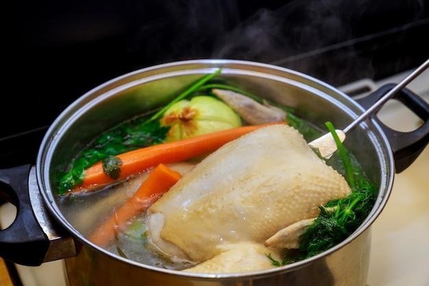 Кипящий куриный бульон с овощами в стальной кастрюле на газовой плите