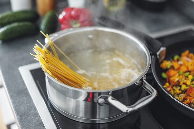 Boiling pot with cooking spaghetti pasta in the kitchen. closeup