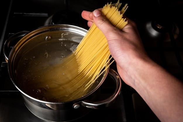 Варка спагетти в кастрюле на плите на кухне.