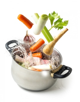 Boiling vegetables flying towards the pot, on white isolated