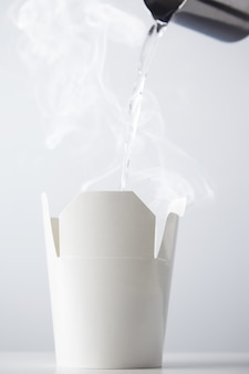 Boiling water being poured from a stainless steel teapot to a white cardboard ramen box container isolated on white