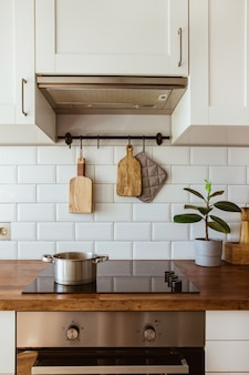 Boiling water in a cooking pot an a pan on a induction stove in the modern white kitchen