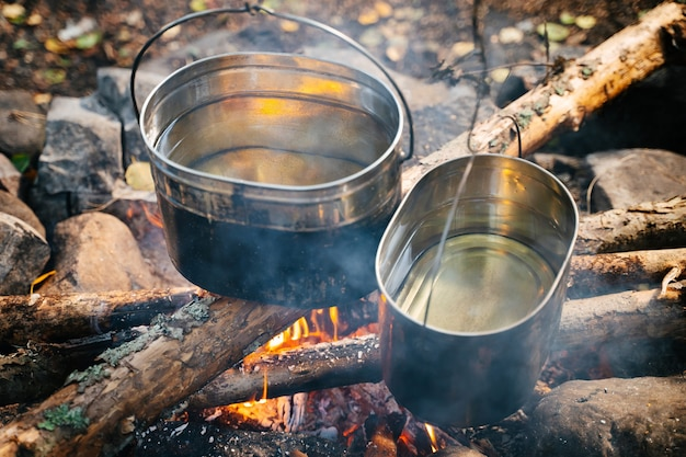 Boiling water in hiking bowlers over a fire in the forest travel and tourism