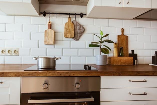 モダンな白いキッチンの電磁調理器の鍋と鍋で水を沸騰させる