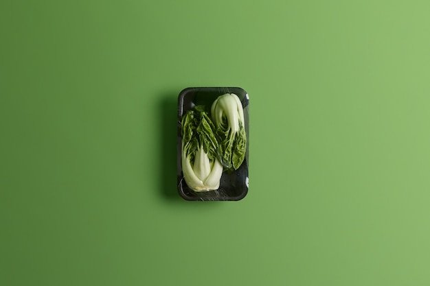 Bok choy or chinese cabbage wrapped with food film on black tray. fresh vegetables for sale in supermarket isolated over green background. healthy lifestyle, refreshment and nutrition concept