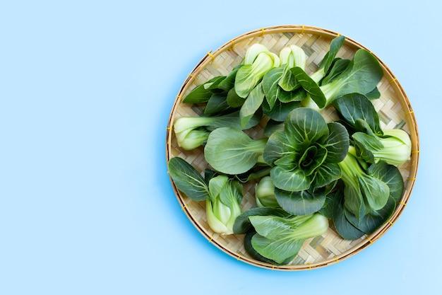 青い表面の竹かごのチンゲン菜