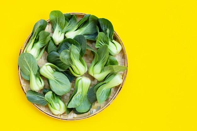 黄色の背景に竹かごのチンゲン菜。