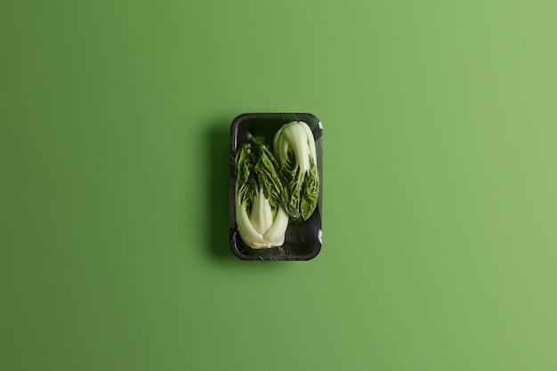 チンゲン菜または白菜を黒いトレイにフードフィルムで包んだもの。緑の背景で隔離のスーパーマーケットで販売されている新鮮な野菜。健康的なライフスタイル、リフレッシュメントと栄養の概念