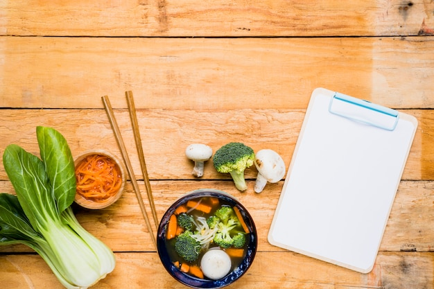 Bokchoy; carrot; fish ball soup; chopsticks and white blank clipboard over the table