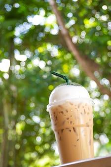 プラストカップの氷のカプチーノ。パッケージを取り除く。緑の性質を持つ飲料bokeh backgr