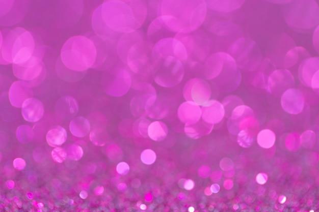 Bokeh defocusedと抽象的なエレガントなピンク紫色の輝きのヴィンテージの輝き