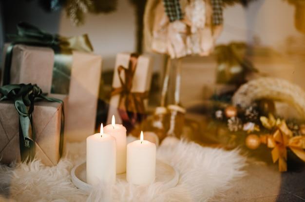Боке подарочные коробки и свечи в комнате украшенный новогодний декор интерьера