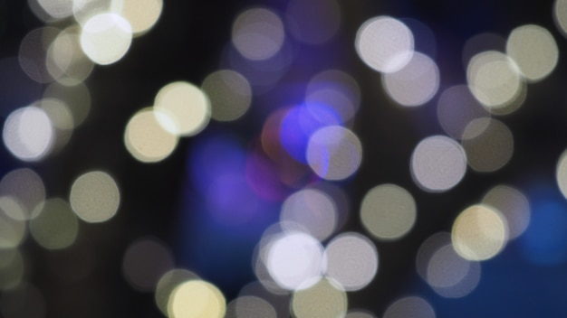 Bokeh images circle bubbles shape blue and light yellow color on black background.