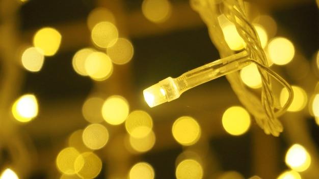 ボケ味の画像は、夜の小さなled電球の黄色い色の円の泡を形作ります。