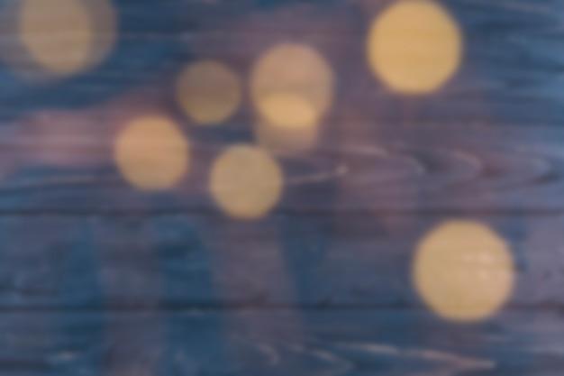 Luci di bokeh su fondo di legno blu