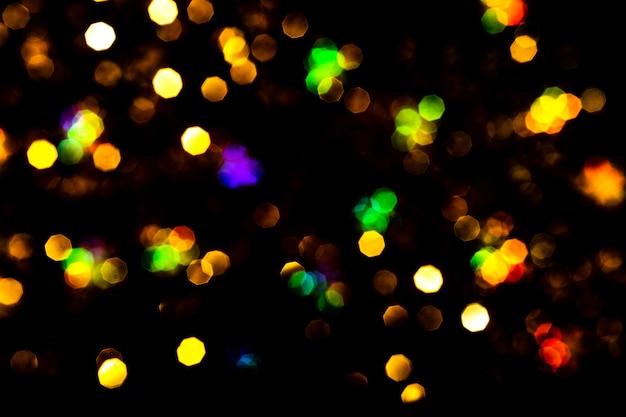Bokeh는 검정에 불이 들어옵니다. 아름 다운 크리스마스 배경, 새 해 개념입니다.
