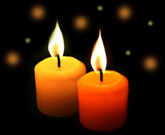 Bokeh yellow candles on black.